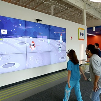 Users playing a motion-sensing game at Do Space's entrance.