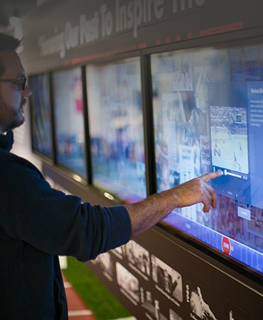 Man using a touch interactive timeline at the Nebraska High School Sports Hall of Fame
