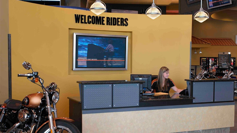 Harley Davidson's in-store digital signage outlines services, prices, and ads for their latest products.