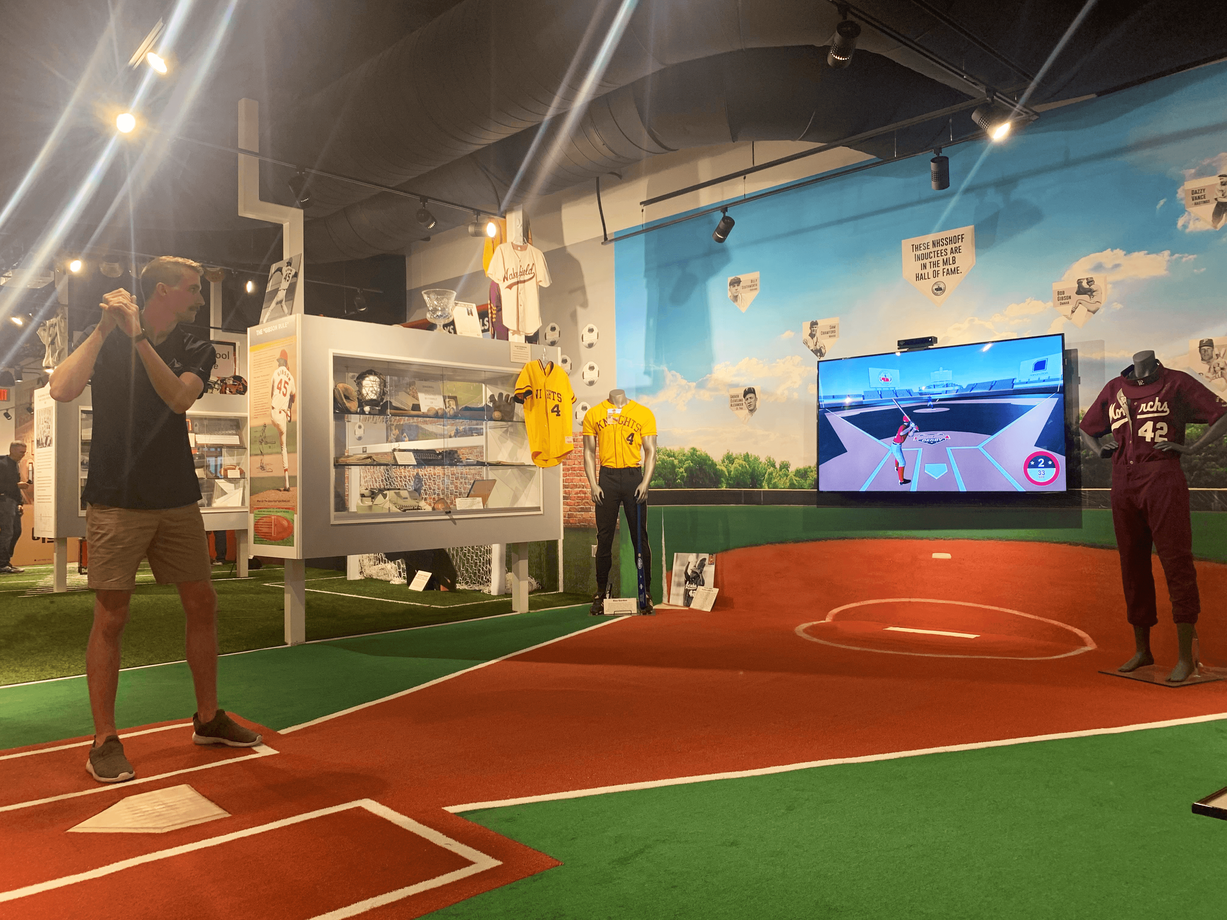 Man standing at home plate playing the gesture-based baseball game at the Nebraska High School Sports Hall of Fame..